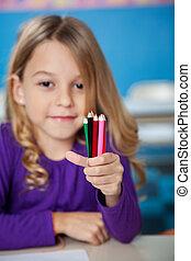 Girl Holding Color Pencils In Kindergarten