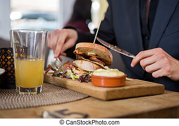 Young Businessman Having Sandwich In Cafe