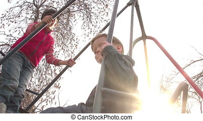 Children on a Swing - Two children ride on a swing. Sun -...