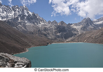 Gokyo Lake - Mountains surrounding the clear blue waters of...