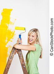 Happy woman painting on ladder - Happy woman painting...