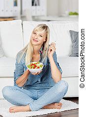 Woman enjoying fruit salad - Smiling female eating a bowl of...