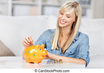 Smiling woman dropping coins into piggy bank - Smiling young...
