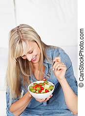 Happy woman eating fresh fruit salad - Happy long haired...