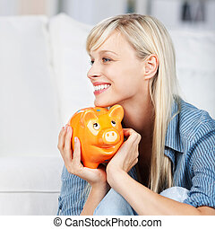 Woman holding piggybank - Side view shot of smiling woman...