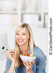 Healthy woman eating fruit salad - Smiling healthy woman...