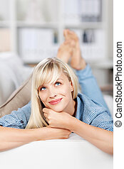 Daydreaming female on sofa - Lying female on couch having...