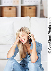 Smiling woman on mobile phone - Smiling woman sitting on the...