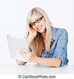 Woman reading the news on a tablet - Attractive blonde woman...