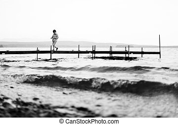 Boy walking on a wharf