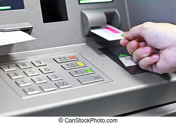 Hand inserting ATM credit card into bank machine to withdraw...