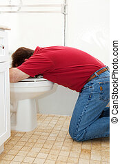 Vomiting in the Toilet - Man in the bathroom, vomiting into...