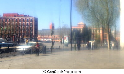 urban scene in madrid reflected in glass mirror wall of the reina sofia museum