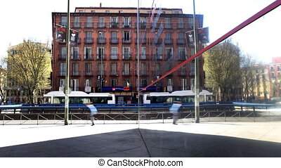 urban scene in madrid reflected in glass mirror wall of the...