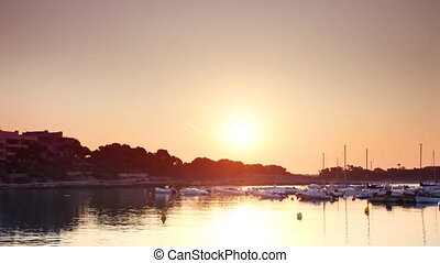 sun rising over the water and harbour of colonia sant jordi...