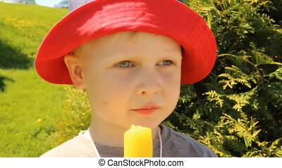 A little boy eating ice cream in a Panama hat on a...