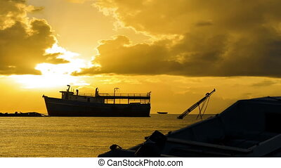 Caribbean Sunrise and Boats - Silhouettes of boats set...