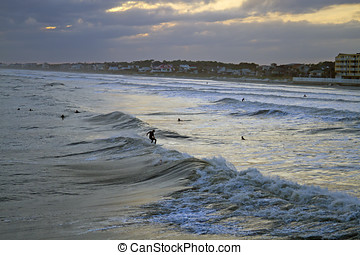 Surfing Before the Storm - Viewed from the sea, surfers surf...