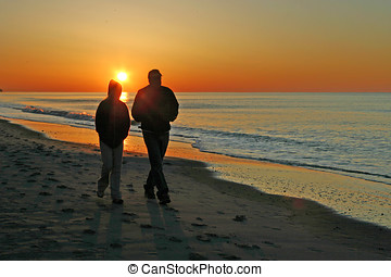 Companionable Beach Stroll - A couple walk together along...