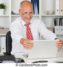happy employee holding his laptop - portrait of happy...
