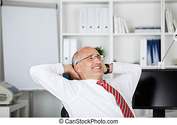 happy businessman leaning back with hands behind his head