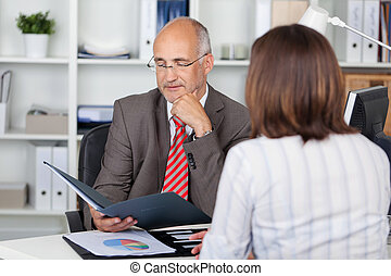 businessman looking at cv - businessman in interview with...