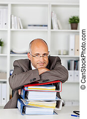 businessman leaning with folded arms on binders -...