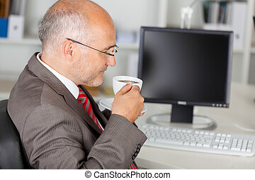 coffee break in the office - businessman having a coffee...