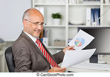Businessman Analyzing Documents At Office Desk - Side view...