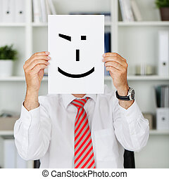 Businessman Holding Wink Smiley In Front Of His Face -...