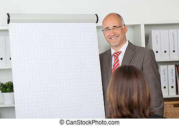 businessman standing at the side of flipchart talking to...