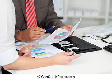 Businesspeople With Graphs At Office Desk - Midsection of...