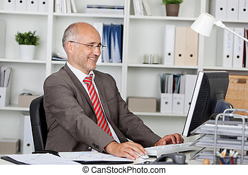 Businessman Using Computer At Desk - Happy mature...