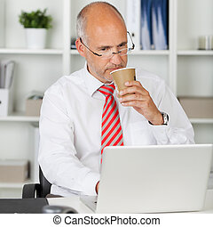 Mature businessman using laptop while drinking coffee in...