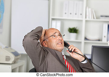desperate businessman using telephone in the office