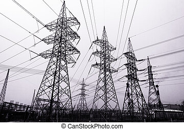 High-voltage power transmission towers in clear blue sky...