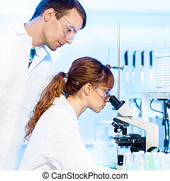 Health care professionals in lab. - Attractive young female...
