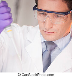 Researcher pipetting in laboratory - Focused life science...