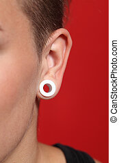 Close up of a woman ear with an ear plug in a red background