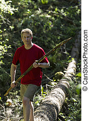 Mature Man hiking over a fallen tree within the woods