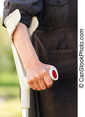 Elderly woman hands resting on the crutch
