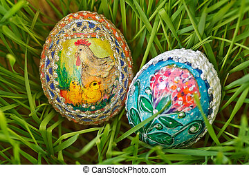 Colorful painted easter eggs between growing green wheat