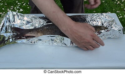 hand wrap fish foil bake - fast scene hands wrap big fish in...