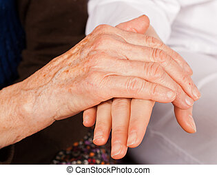 Young doctor holds the elderly woman hands - Young sweet...