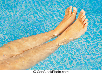 Young woman's feet in a swimming pool - Young sweet woman's...