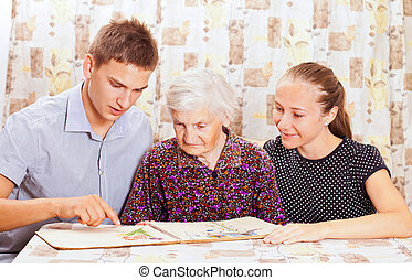 Elderly woman with the two young smileing grandchild -...
