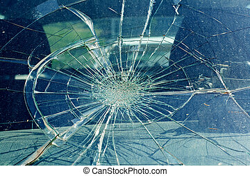 The broken windshield in the car accident - the broken...