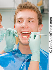 Cheerful patient - Young happy man at the sweet dentist