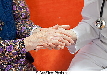 Young sweet doctor holds the old womans hand - Young doctor...