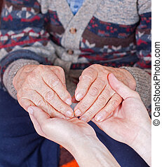 Young doctor holds old man's hands - Young doctor holds the...
